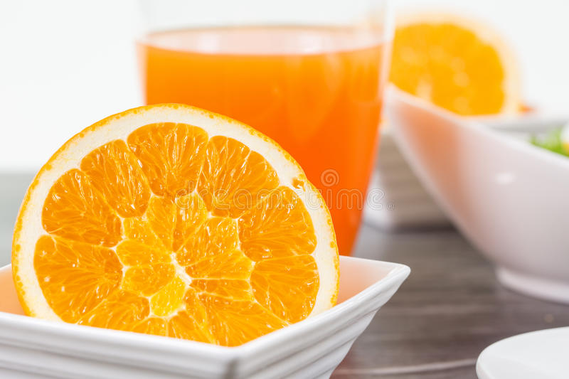 Half cutted orange fruit in a bowl stock images