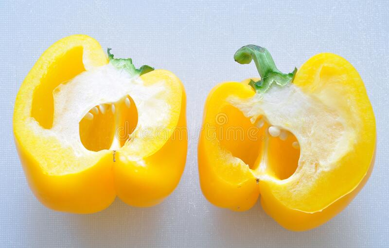 Half cutted Yellow Capsicum on chopping board background stock photo