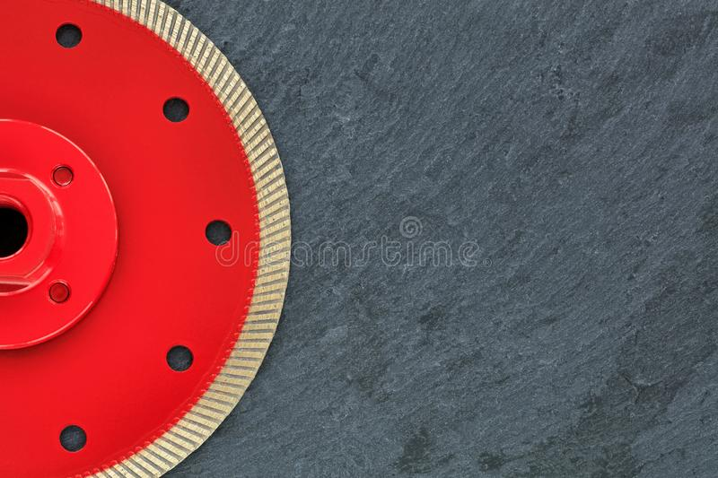 Half of the diamond cutting wheel is red with a threaded nut on a background of gray granite. Half of the diamond cutting wheel is red with a threaded nut, on royalty free stock images