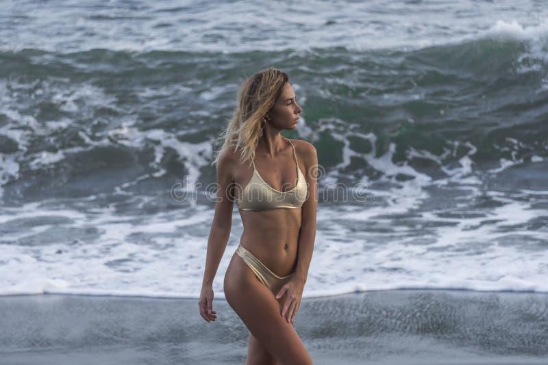 Half die gezicht van leuke jonge vrouw in gouden bikini op achtergrond van stormachtige oceaan wordt geschoten royalty-vrije stock afbeeldingen