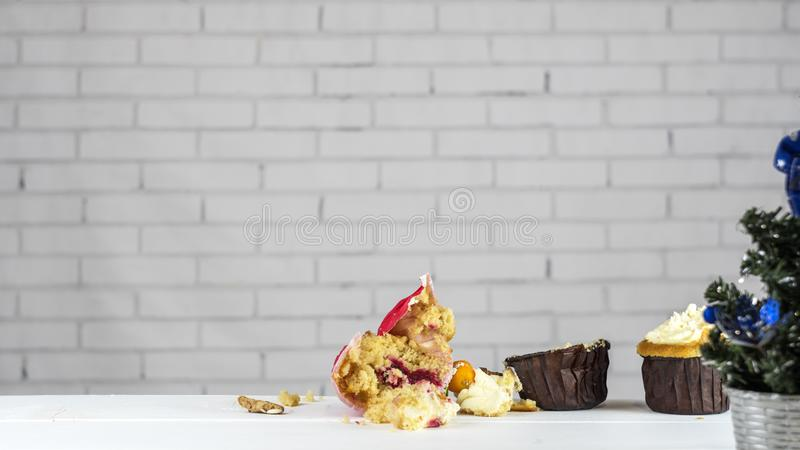 Half-eaten cupcake on the table with a Christmas tree. Christmas is over stock photos