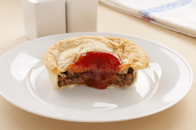 Half Eaten Meat Pie. With ketchup dripping down the front royalty free stock photo