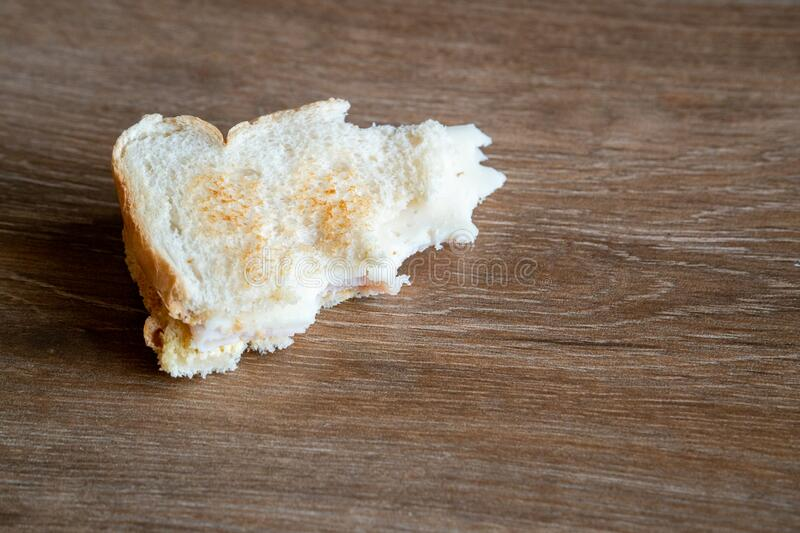 Half Eaten Sandwich thrown on the floor. Discarded Sandwich. Bread tossed to the floor. Thrown into the trash food. Concept.  royalty free stock image