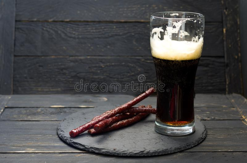 A half-empty glass of beer. Dark beer and sausages. stock images