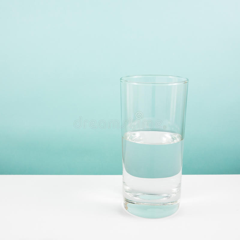Half empty or half full glass of water on white table. (For positive thinking). Half empty or half full glass of water on white table. (For positive thinking royalty free stock images