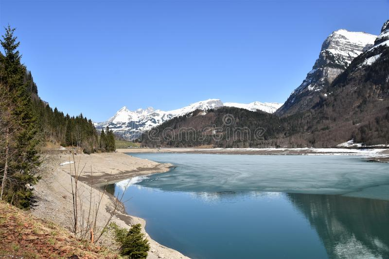 Half-empty Klöntalersee lake covered partly with ice and reflection of Alps with snow. Half-empty lake covered partly with ice and reflection of Alps with stock photos