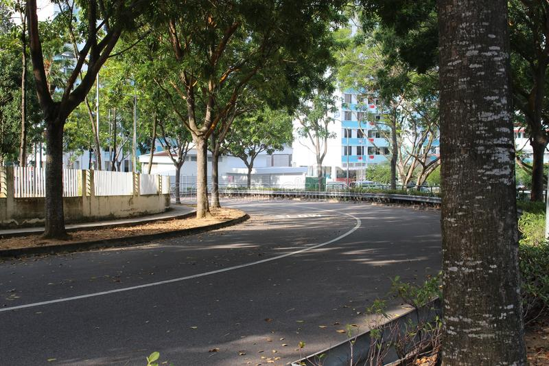 A half empty road in Singapore. A photo of a road with no moving traffic but lots of parking vehicles royalty free stock photography