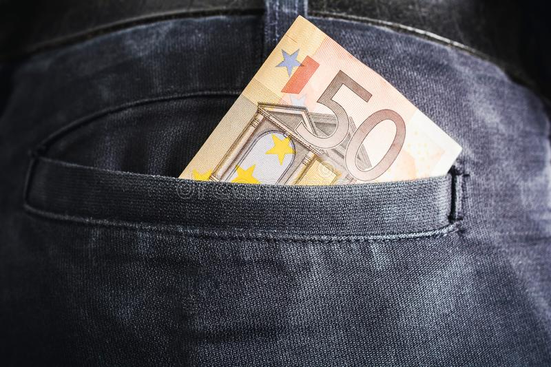 Half Of A 50 Euro Bill Showing Out Of The Back Pocket Of A Black Jeans Trouser - Rich Man Concept. The Half Of A 50 Euro Bill Showing Out Of The Back Pocket Of A stock images