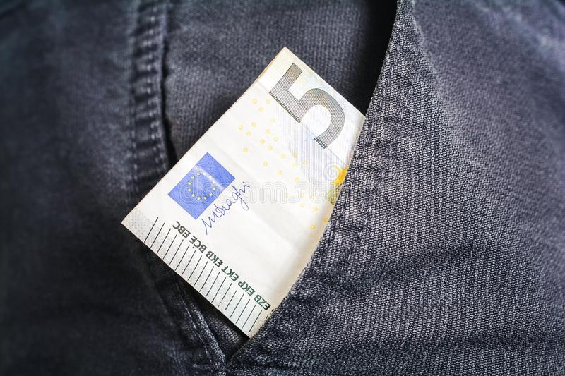Half Of A 5 Euro Bill Showing Out Of The Pocket Of A Black Jeans Trouser - Poor Man Concept. Half Of A 5 Euro Bill Showing Out Of The Pocket Of Black Jeans royalty free stock photography