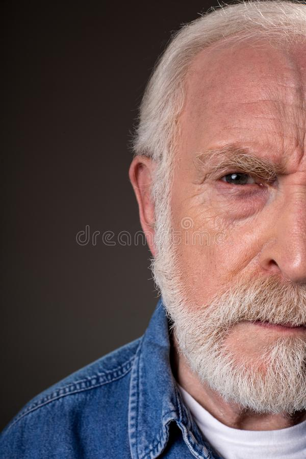 Serious old male demonstrating distrust. Half face of aging male looking at camera with suspicion. on grey background. Close up stock image