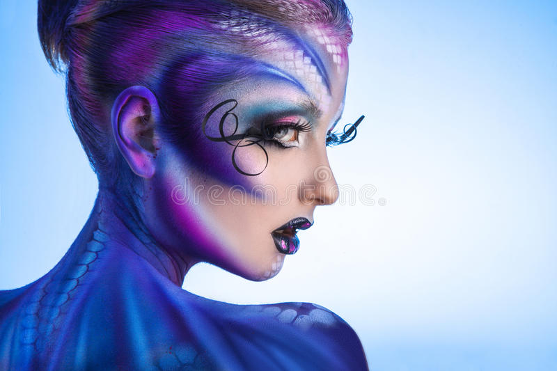 Half face portrait of fashion model with creative make up. Looking away in studio on blue background royalty free stock images