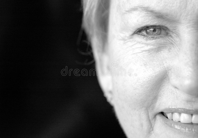 Half face senior woman. Close up of half the face of a senior woman smiling in black and white royalty free stock photo