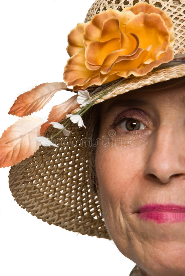 Half face senior woman with sun hat stock photography