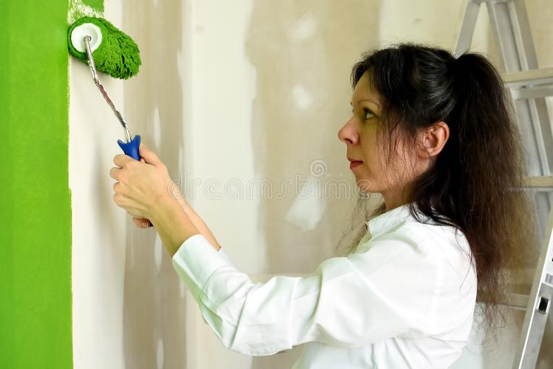Profile of a smiling pretty young woman is keeping roller with two hands and  carefully trying to paint green interior wall in a royalty free stock image