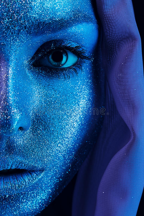 Half face of woman in blue and violet bodyart. In studio stock image