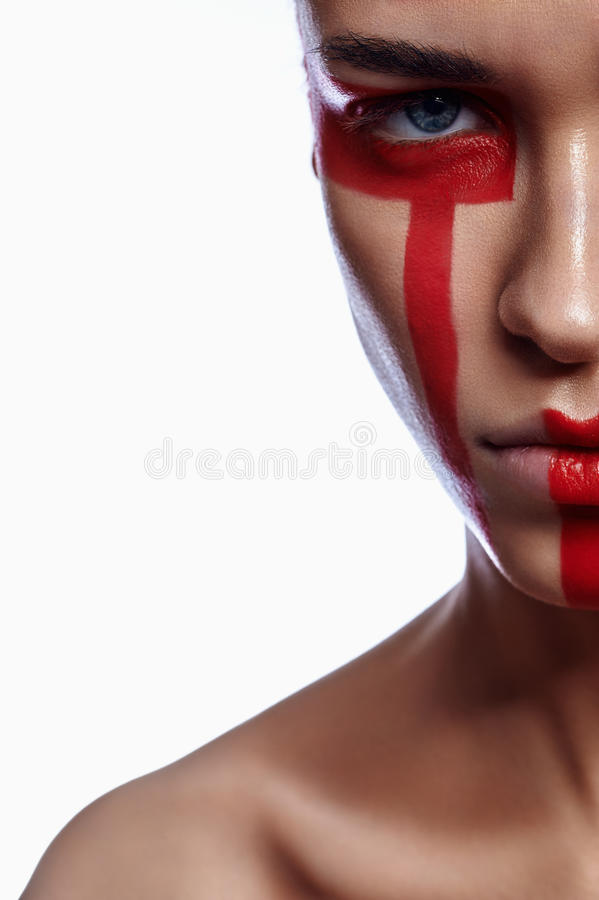 Half Face of Woman with tribalistic red Make-up stock image