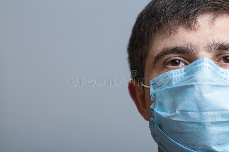 Half face of young doctor in protectivel mask looking straight with hope and confidence, concept of medicine and health stock image