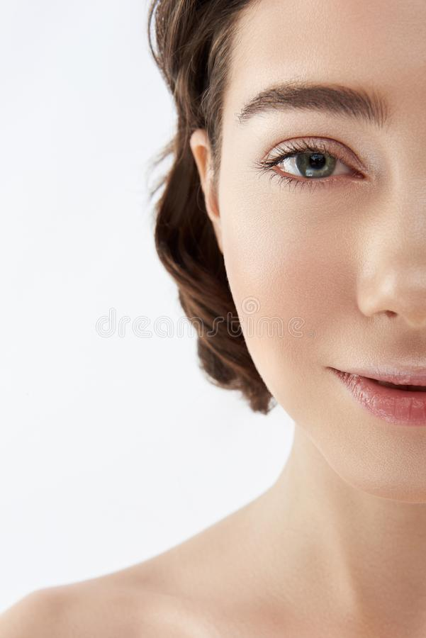 Half face of young smiling pretty brunette female royalty free stock images