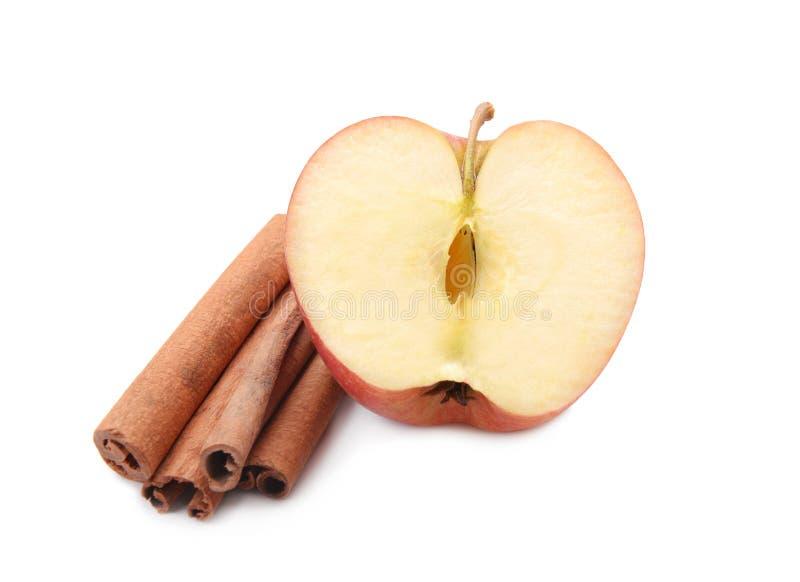 Half of fresh apple and cinnamon sticks on white background stock image