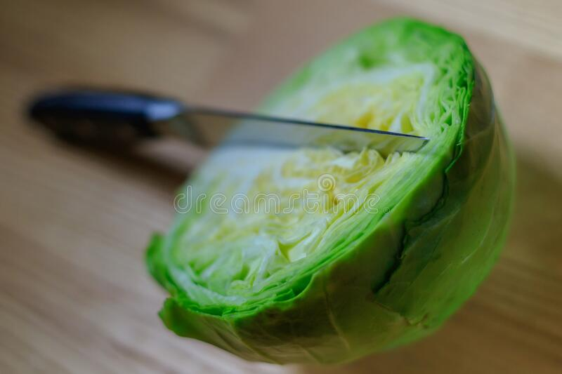 Half fresh green cabbage on a wooden board with a kitchen knife royalty free stock images