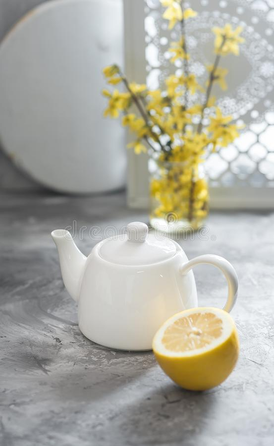 Half of fresh lemon and white teapot are on gray background stock photo