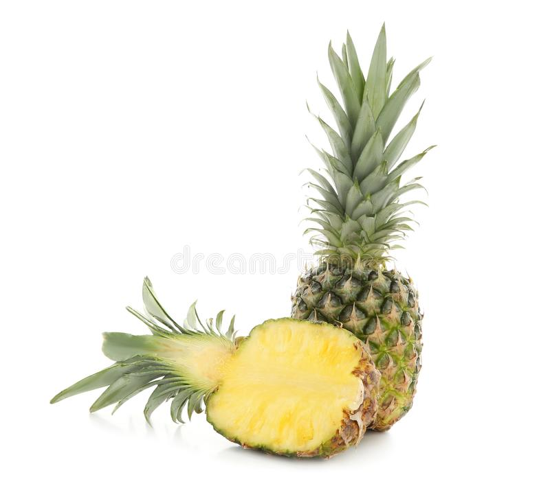 Half of fresh ripe pineapple and whole fruit on white background royalty free stock photos