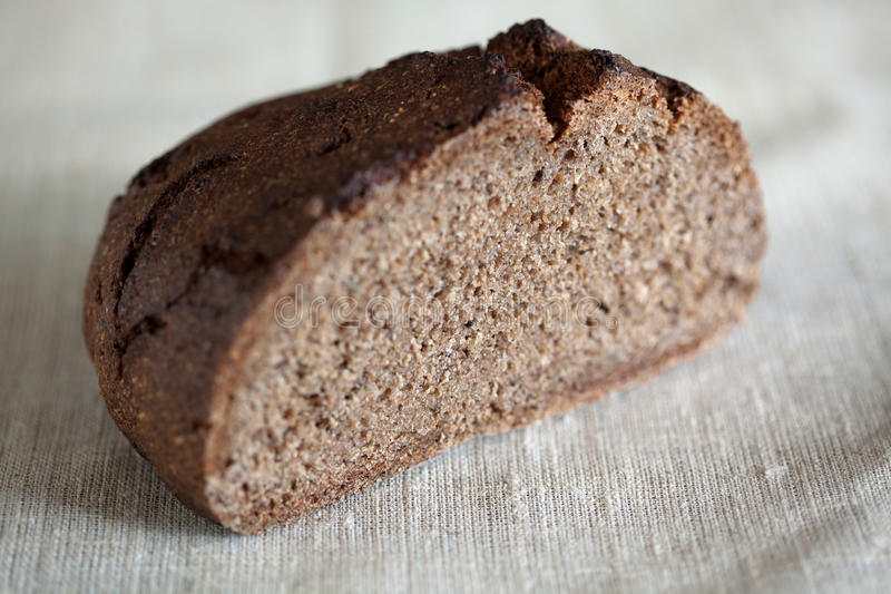 Half of freshly baked rustic, sourdough rye loaf of bread stock image