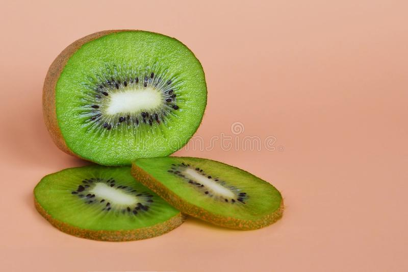 Half fruit and two green slices of kiwi, healthy eating concept on an orange background copy space stock photo