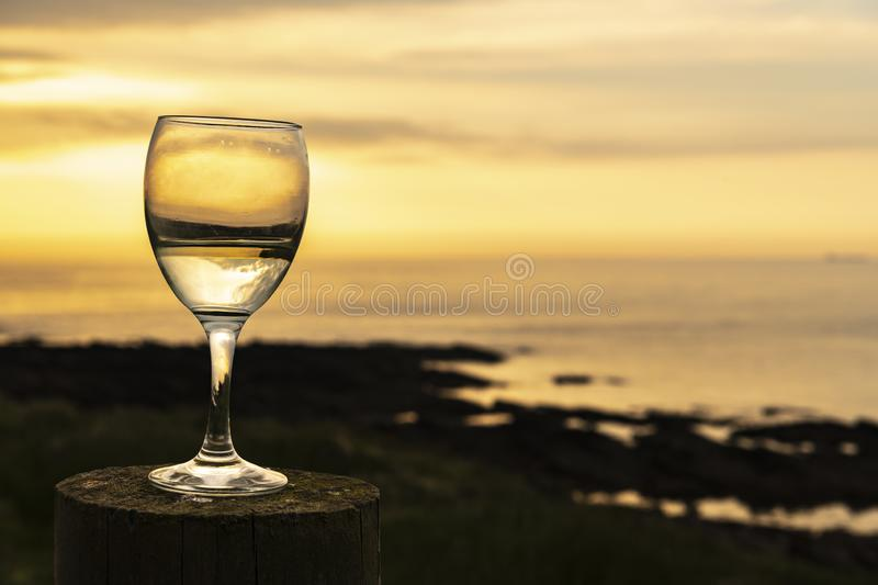 Half Full or half empty white. A wine glass half full of wine on a wooden post with the sun setting over the Pentland Firth, Caithness, Scotland. 01 June 2018 royalty free stock image