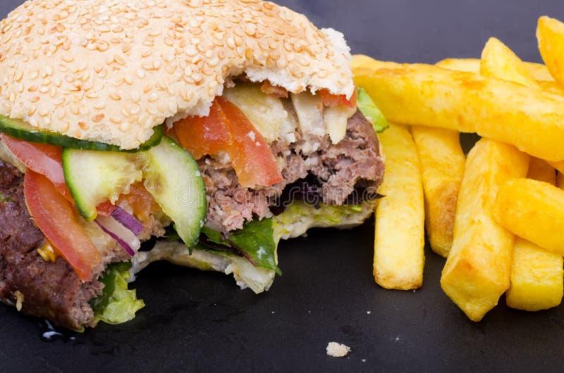 Half Gegeten Cheeseburger en Gebraden gerechten royalty-vrije stock foto's
