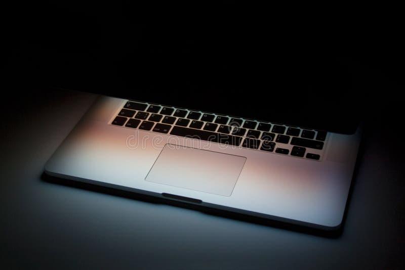 Half gesloten laptop met het schermlicht op donkere achtergrond stock afbeelding
