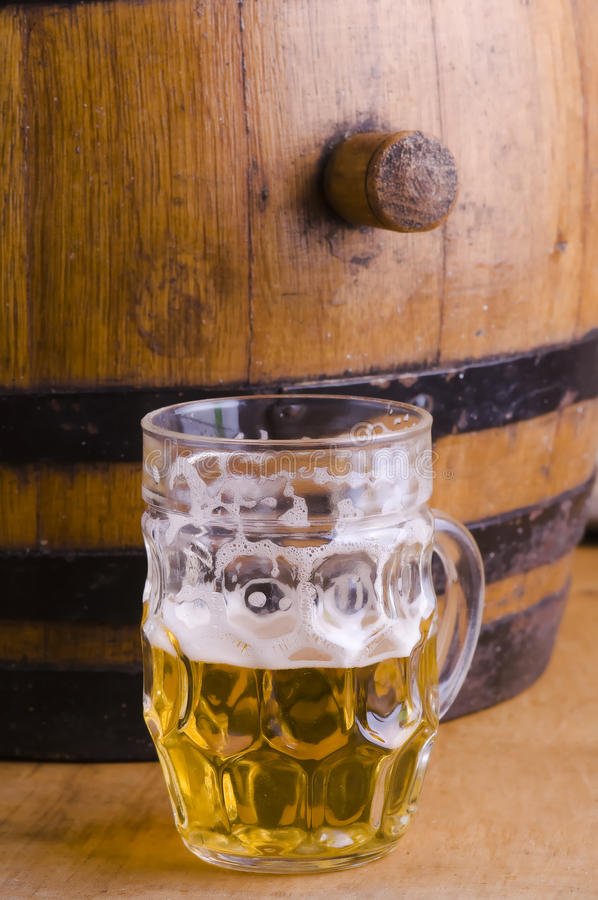 Half glass beer. Glass of beer, half empty with wooden barrel, blond beer with foam royalty free stock image