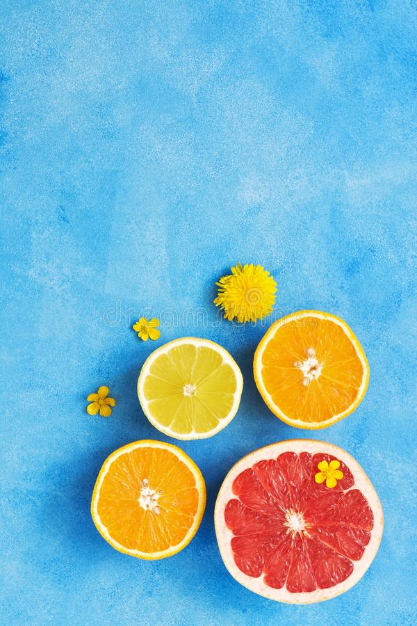 Half of the grapefruit, lemon and orange are decorated with small yellow flowers on a blue background. View from above, copy space royalty free stock photography