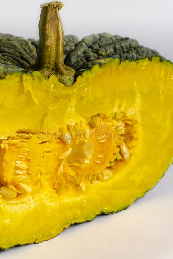 Half green pumpkin with yellow flesh on a white background royalty free stock photos