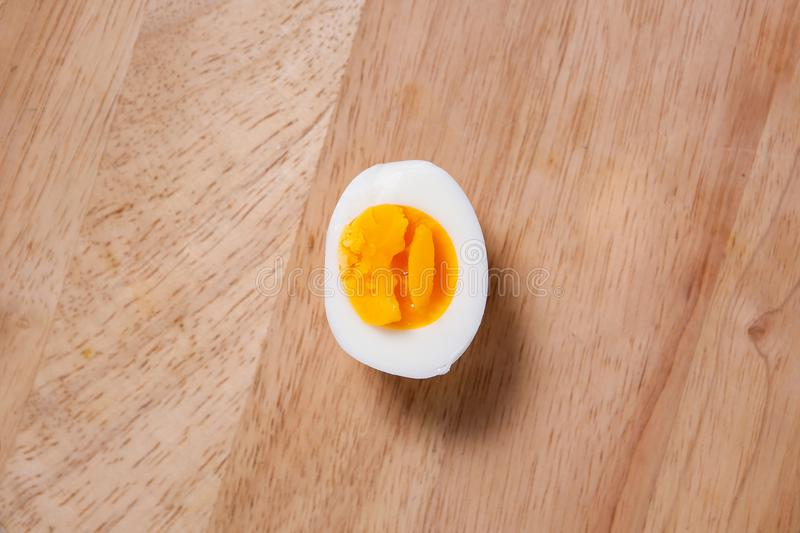 Half of the hard boiled egg. On wooden background royalty free stock image