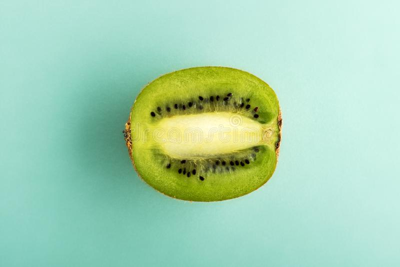 Half of the kiwi on cyan background. Half of ripe green kiwi fruit isolated in center on cyan background. Viewed from above in close-up stock photo