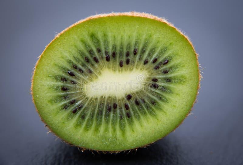 half kiwi Grön söt frukt på mörk bakgrund royaltyfri bild
