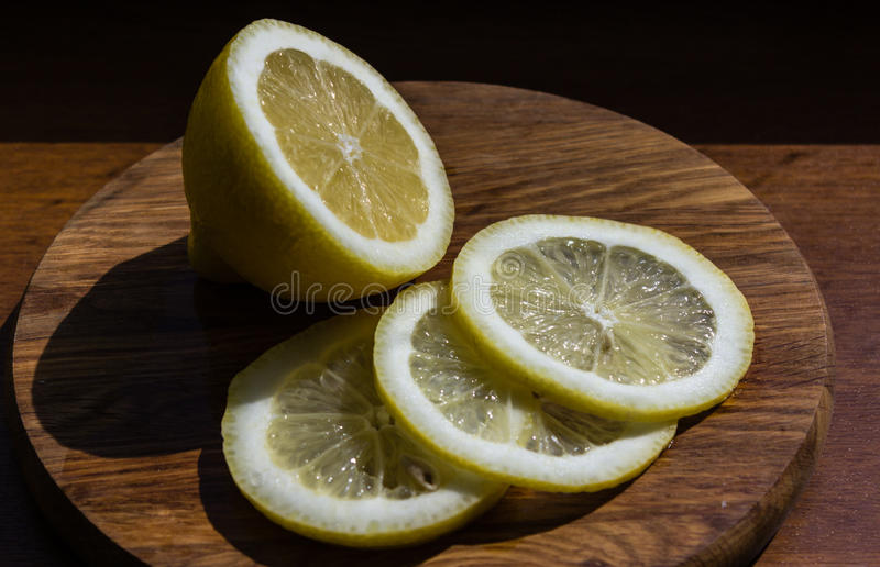 Half of lemon and slices on a cutting board royalty free stock images