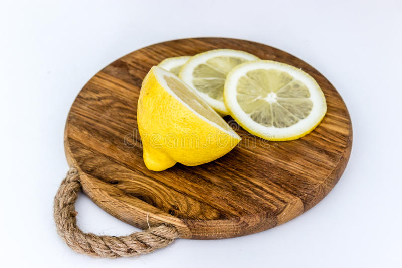 Half of lemon and slices on wooden cutting board royalty free stock photo