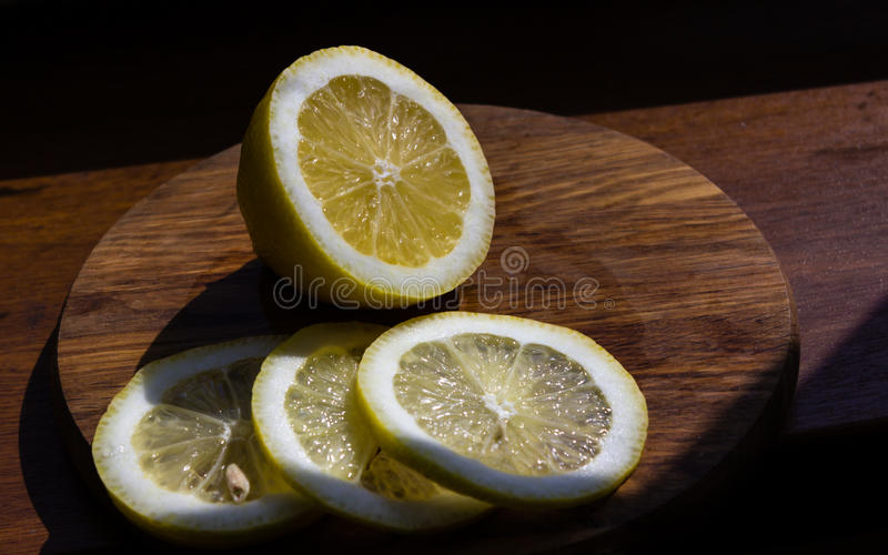 Half of lemon and three slices on a cutting board royalty free stock images
