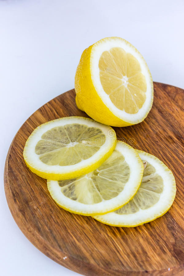 Half of lemon and three slices on wooden cutting board royalty free stock photos