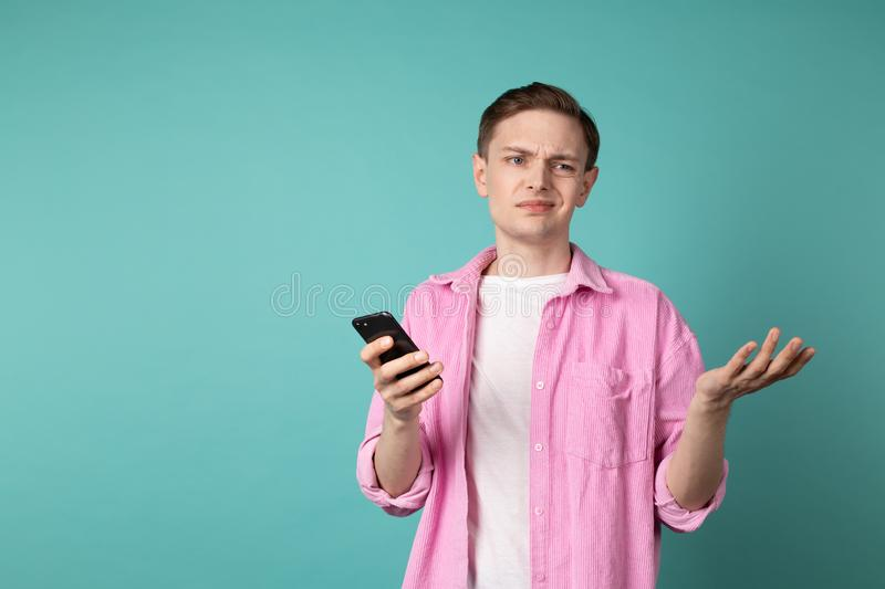 Half lenght portrait of a confused unhappy man in pink shirt stock image