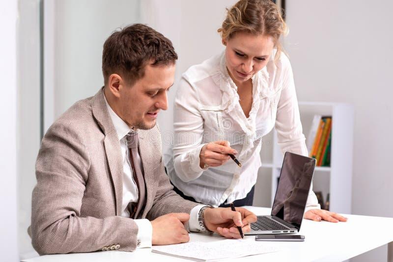 Half lengteportret van de jonge mens die beige kostuumzitting dragen die aan zijn laptop werken Een vrouw, een collega, bespreekt stock afbeeldingen