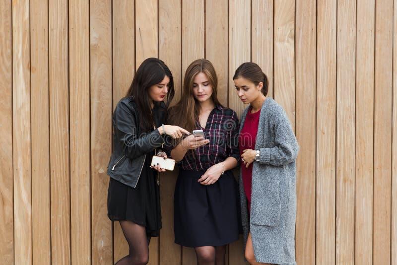 Half lengteportret van een jonge modieuze hipstermeisjes die slimme telefoon voor navigatie met behulp van vóór begin hun buiten  royalty-vrije stock foto's