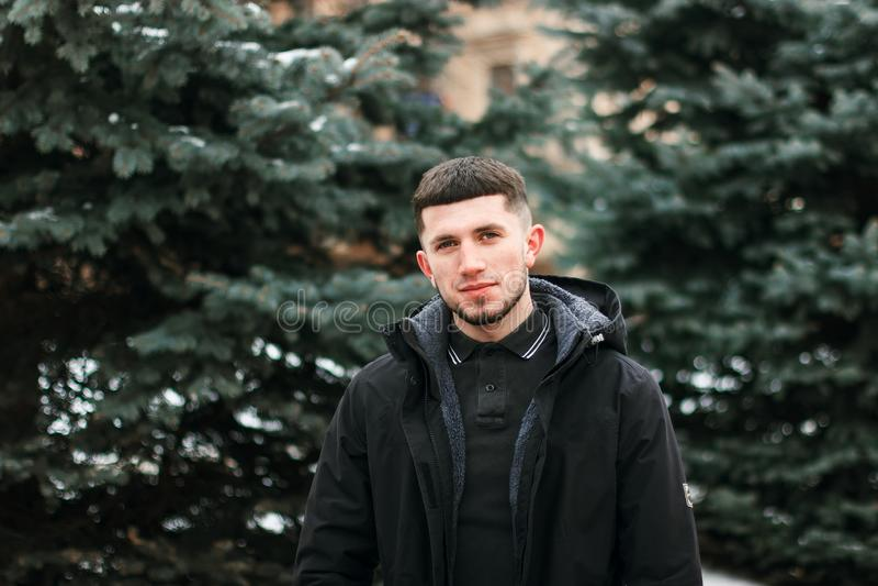 Half lengteportret van jonge brutale kerel met baard in zwart de winterjasje royalty-vrije stock foto