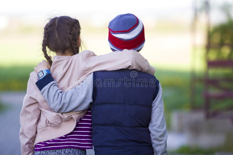 Half-length back view of two children, girl with long dark braids and boy hugging each other over shoulders on blurred outdoors stock photos
