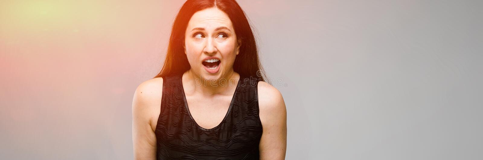 Portrait of emotional pretty confident puzzled astonished plus size model standing in studio on gray background royalty free stock photo