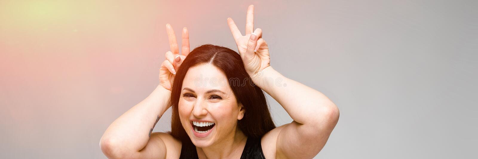 Emotional pretty confident funny plus size model standing in studio fooling on gray background stock photography
