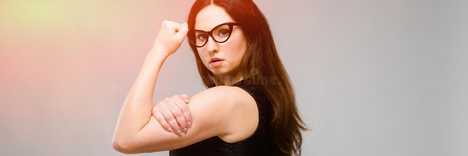 Emotional pretty confident plus size model in glasses showing her strength standing in studio on gray background royalty free stock photography