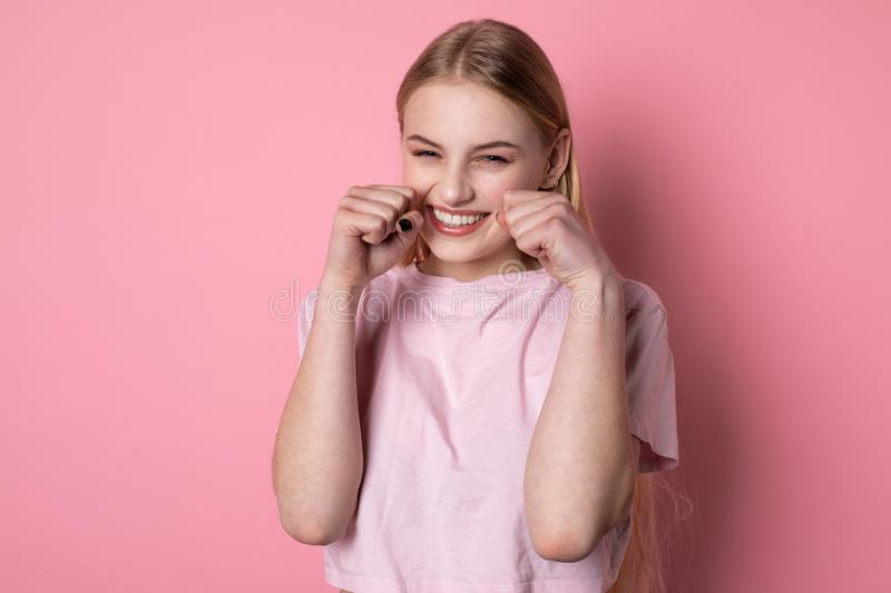 Half length portrait of beautiful blonde girl with blue eyes, wearing pink t-shirt, with fists near face royalty free stock image
